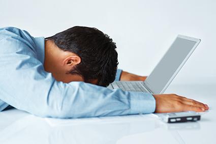Un hombre desmotivado por un intento de fraude online delante de una pantalla