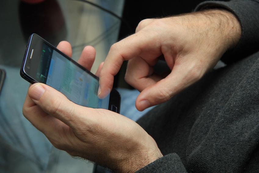 Un hombre navegando con su smartphone velando por su protección de datos - Conversia